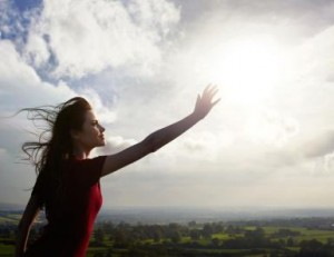 Young woman reaching for the sun in countryside.